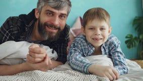 Πορτρέτο κινηματογραφήσεων σε πρώτο πλάνο του ενήλικου πατέρα δύο ανθρώπων και χαριτωμένος λίγος γιος που βρίσκεται στο κρεβάτι σ απόθεμα βίντεο