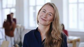 Πορτρέτο κινηματογραφήσεων σε πρώτο πλάνο του ευτυχούς επαγγελματικού θηλυκού προϊσταμένου με τα ξανθά μαλλιά στα επίσημα ενδύματ απόθεμα βίντεο