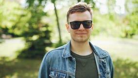 Πορτρέτο κινηματογραφήσεων σε πρώτο πλάνο του εύθυμου νεαρού άνδρα στα γυαλιά ηλίου που φορούν το σακάκι τζιν που εξετάζει τη κάμ απόθεμα βίντεο