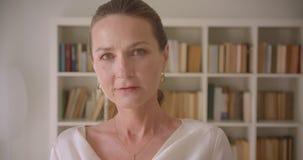 Πορτρέτο κινηματογραφήσεων σε πρώτο πλάνο του ηλικιωμένου καυκάσιου θηλυκού brunette που εξετάζει τη κάμερα που χαμογελά στη βιβλ απόθεμα βίντεο