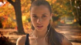 Πορτρέτο κινηματογραφήσεων σε πρώτο πλάνο του κουρασμένου καυκάσιου κοριτσιού με τα ακουστικά που προσέχει στη κάμερα που πιάνει  απόθεμα βίντεο