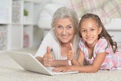 Πορτρέτο κινηματογραφήσεων σε πρώτο πλάνο του μικρού κοριτσιού με τη γιαγιά της που χρησιμοποιεί το lap-top στοκ εικόνα