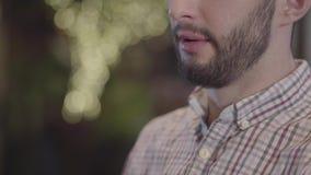 Πορτρέτο κινηματογραφήσεων σε πρώτο πλάνο του μισού προσώπου του γενειοφόρου κρασιού κατανάλωσης τύπων και κάπνισμα hookah φιλμ μικρού μήκους