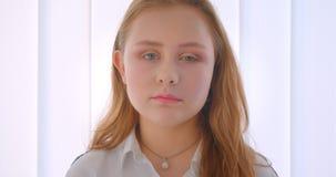Πορτρέτο κινηματογραφήσεων σε πρώτο πλάνο του νέου αρκετά καυκάσιου κοριτσιού που εξετάζει τη κάμερα στο εσωτερικό στο άσπρο δωμά φιλμ μικρού μήκους