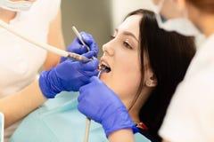 Πορτρέτο κινηματογραφήσεων σε πρώτο πλάνο του νέου ασθενή γυναικών, που κάθεται στην καρέκλα οδοντιάτρων Ο γιατρός εξετάζει τα δό στοκ εικόνα