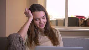 Πορτρέτο κινηματογραφήσεων σε πρώτο πλάνο του νέου ελκυστικού καυκάσιου θηλυκού χρησιμοποιώντας το lap-top και προσέχοντας έναν α απόθεμα βίντεο