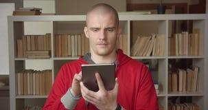 Πορτρέτο κινηματογραφήσεων σε πρώτο πλάνο του νέου ελκυστικού καυκάσιου άνδρα σπουδαστή χρησιμοποιώντας την ταμπλέτα και παρουσιά απόθεμα βίντεο