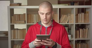 Πορτρέτο κινηματογραφήσεων σε πρώτο πλάνο του νέου ελκυστικού καυκάσιου άνδρα σπουδαστή που χρησιμοποιεί την ταμπλέτα στη βιβλιοθ απόθεμα βίντεο