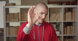 Πορτρέτο κινηματογραφήσεων σε πρώτο πλάνο του νέου ελκυστικού καυκάσιου άνδρα σπουδαστή που παρουσιάζει εντάξει σημάδι που εξετάζ φιλμ μικρού μήκους