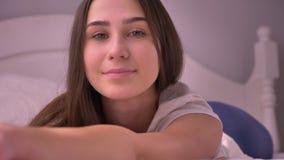 Πορτρέτο κινηματογραφήσεων σε πρώτο πλάνο του νέου ζαλίζοντας καυκάσιου θηλυκού που βρίσκεται στο κρεβάτι και που εξετάζει το χαμ απόθεμα βίντεο