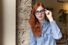 Πορτρέτο κινηματογραφήσεων σε πρώτο πλάνο του νέου κοκκινομάλλους κοριτσιού με τα γυαλιά, στάση στοκ φωτογραφία με δικαίωμα ελεύθερης χρήσης