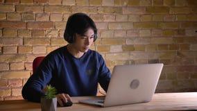 Πορτρέτο κινηματογραφήσεων σε πρώτο πλάνο του νέου κορεατικού επιχειρηματία στα ακουστικά που έχουν μια τηλεοπτική κλήση στο lap- φιλμ μικρού μήκους