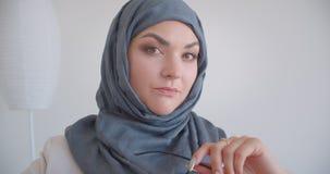 Πορτρέτο κινηματογραφήσεων σε πρώτο πλάνο του νέου μουσουλμανικού θηλυκού γιατρού στο hijab που εξετάζει eyeglasses εκμετάλλευσης απόθεμα βίντεο