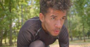 Πορτρέτο κινηματογραφήσεων σε πρώτο πλάνο του νέου φίλαθλου αρσενικού αφροαμερικάνων jogger που προετοιμάζεται να τρέξει στο πάρκ απόθεμα βίντεο
