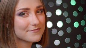 Πορτρέτο κινηματογραφήσεων σε πρώτο πλάνο του νέου χαριτωμένου καυκάσιου κοριτσιού που εξετάζει τη κάμερα και που χαμογελά χαρωπά απόθεμα βίντεο