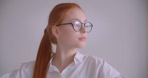 Πορτρέτο κινηματογραφήσεων σε πρώτο πλάνο του νέου χαριτωμένου καυκάσιου redhead θηλυκού που εξετάζει τη κάμερα που βάζει στα γυα απόθεμα βίντεο