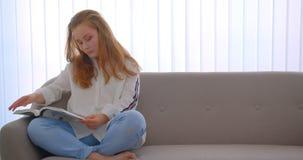 Πορτρέτο κινηματογραφήσεων σε πρώτο πλάνο του νέου χαριτωμένου καυκάσιου κοριτσιού που διαβάζει μια συνεδρίαση βιβλίων στον καναπ απόθεμα βίντεο