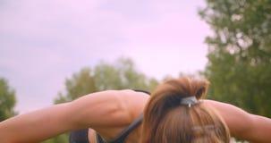 Πορτρέτο κινηματογραφήσεων σε πρώτο πλάνο του νέου χαριτωμένου φίλαθλου κοριτσιού ικανότητας που κάνει την ώθηση UPS στο πάρκο στ φιλμ μικρού μήκους