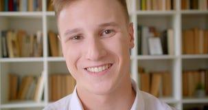 Πορτρέτο κινηματογραφήσεων σε πρώτο πλάνο του νέου όμορφου καυκάσιου άνδρα σπουδαστή που χαμογελά ευτυχώς να εξετάσει τη κάμερα σ φιλμ μικρού μήκους