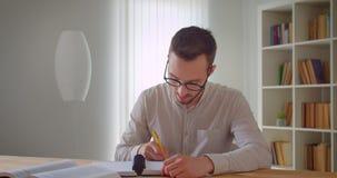 Πορτρέτο κινηματογραφήσεων σε πρώτο πλάνο του νέου όμορφου καυκάσιου άνδρα σπουδαστή eyeglasses που μελετούν και που χρησιμοποιού απόθεμα βίντεο