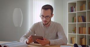 Πορτρέτο κινηματογραφήσεων σε πρώτο πλάνο του νέου όμορφου καυκάσιου επιχειρηματία eyeglasses που χρησιμοποιούν την ταμπλέτα στο  απόθεμα βίντεο