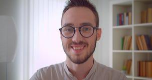 Πορτρέτο κινηματογραφήσεων σε πρώτο πλάνο του νέου όμορφου καυκάσιου άνδρα σπουδαστή eyeglasses που εξετάζει τη κάμερα που χαμογε φιλμ μικρού μήκους