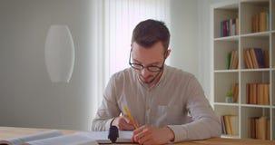 Πορτρέτο κινηματογραφήσεων σε πρώτο πλάνο του νέου όμορφου καυκάσιου άνδρα σπουδαστή eyeglasses που μελετούν και που χρησιμοποιού φιλμ μικρού μήκους