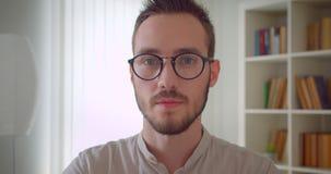 Πορτρέτο κινηματογραφήσεων σε πρώτο πλάνο του νέου όμορφου καυκάσιου άνδρα σπουδαστή eyeglasses που εξετάζει τη κάμερα στο διαμέρ απόθεμα βίντεο