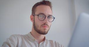 Πορτρέτο κινηματογραφήσεων σε πρώτο πλάνο του νέου όμορφου καυκάσιου επιχειρηματία eyeglasses που δακτυλογραφούν στο lap-top που  απόθεμα βίντεο