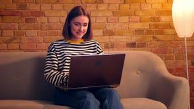 Πορτρέτο κινηματογραφήσεων σε πρώτο πλάνο του νέου όμορφου κοριτσιού που χρησιμοποιεί τη συνεδρίαση lap-top στον καναπέ σε ένα άν απόθεμα βίντεο