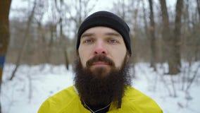 Πορτρέτο κινηματογραφήσεων σε πρώτο πλάνο του νεαρού άνδρα με τα μπλε μάτια και της γενειάδας στο χιονώδες χειμερινό δάσος απόθεμα βίντεο