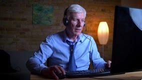 Πορτρέτο κινηματογραφήσεων σε πρώτο πλάνο του παλαιού καυκάσιου blogger που παίζει τα τηλεοπτικά παιχνίδια στον υπολογιστή και τη απόθεμα βίντεο