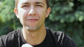 Πορτρέτο κινηματογραφήσεων σε πρώτο πλάνο του πεινασμένου νεαρού άνδρα που τρώει το παγωτό απόθεμα βίντεο