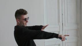 Πορτρέτο κινηματογραφήσεων σε πρώτο πλάνο του συναισθηματικού χορεύοντας ατόμου, ενώ ακούει τη μουσική στα ακουστικά Κυματίζει, τ απόθεμα βίντεο