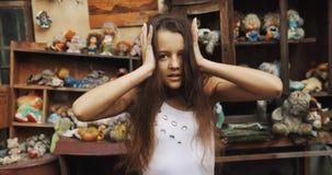Πορτρέτο κινηματογραφήσεων σε πρώτο πλάνο του υ μικρού κοριτσιού με τη μακριά σκοτεινή τρίχα nerveously σχετικά με το κεφάλι της  απόθεμα βίντεο