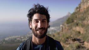 Πορτρέτο κινηματογραφήσεων σε πρώτο πλάνο του χαμογελώντας αρσενικού οδοιπόρου στο βουνό φιλμ μικρού μήκους