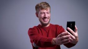 Πορτρέτο κινηματογραφήσεων σε πρώτο πλάνο του χαμογελώντας ευτυχούς μέσης ηλικίας καυκάσιου ατόμου που παίρνει selfies στο τηλέφω φιλμ μικρού μήκους