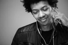 Πορτρέτο κινηματογραφήσεων σε πρώτο πλάνο του όμορφου ατόμου αφροαμερικάνων που ακούει τη μουσική Στοκ Εικόνα