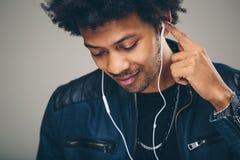 Πορτρέτο κινηματογραφήσεων σε πρώτο πλάνο του όμορφου ατόμου αφροαμερικάνων που ακούει τη μουσική Στοκ Φωτογραφία