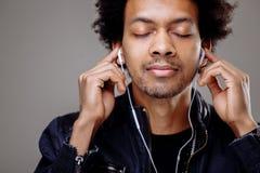 Πορτρέτο κινηματογραφήσεων σε πρώτο πλάνο του όμορφου ατόμου αφροαμερικάνων που ακούει τη μουσική Στοκ φωτογραφία με δικαίωμα ελεύθερης χρήσης
