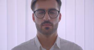 Πορτρέτο κινηματογραφήσεων σε πρώτο πλάνο του όμορφου επιτυχούς καυκάσιου επιχειρηματία eyeglasses που εξετάζει τη κάμερα στο άσπ φιλμ μικρού μήκους