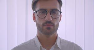 Πορτρέτο κινηματογραφήσεων σε πρώτο πλάνο του όμορφου επιτυχούς καυκάσιου επιχειρηματία eyeglasses που γυρίζουν και που εξετάζουν φιλμ μικρού μήκους
