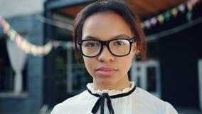 Πορτρέτο κινηματογραφήσεων σε πρώτο πλάνο του όμορφου κοριτσιού αφροαμερικάνων με το σοβαρό πρόσωπο υπαίθρια φιλμ μικρού μήκους