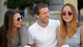 Πορτρέτο κινηματογραφήσεων σε πρώτο πλάνο τριών χαμογελώντας φίλων που κάθονται με τα φλιτζάνια του καφέ υπαίθρια και που μιλούν  απόθεμα βίντεο