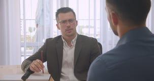 Πορτρέτο κινηματογραφήσεων σε πρώτο πλάνο των ελκυστικών επιχειρηματιών eyeglasses που έχουν μια συνέντευξη εργασίας στο γραφείο  φιλμ μικρού μήκους