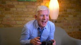 Πορτρέτο κινηματογραφήσεων σε πρώτο πλάνο των παλαιών καυκάσιων businessmanplaying τηλεοπτικών παιχνιδιών και της νίκης όντας ευτ απόθεμα βίντεο