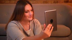 Πορτρέτο κινηματογραφήσεων σε πρώτο πλάνο των υπέρβαρων χαρούμενων θηλυκών πρότυπων συζητήσεων ενεργά και παθιασμένα στην ταμπλέτ απόθεμα βίντεο
