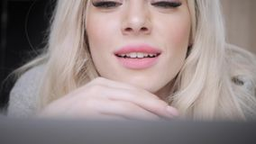 Πορτρέτο κινηματογραφήσεων σε πρώτο πλάνο όμορφο ξανθό να βρεθεί γυναικών στο κρεβάτι με το γκρίζο lap-top αργιλίου Χαμόγελα κορι απόθεμα βίντεο
