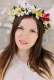 Πορτρέτο κινηματογραφήσεων σε πρώτο πλάνο - γυναίκα brunette στο floral στεφάνι των ορχιδεών και του λεπτού άσπρου φορέματος Στοκ φωτογραφία με δικαίωμα ελεύθερης χρήσης