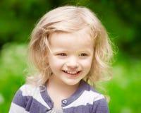Πορτρέτο κινηματογραφήσεων σε πρώτο πλάνο ενός χαμογελώντας ξανθού μικρού κοριτσιού με τη σγουρή τρίχα Στοκ Φωτογραφίες